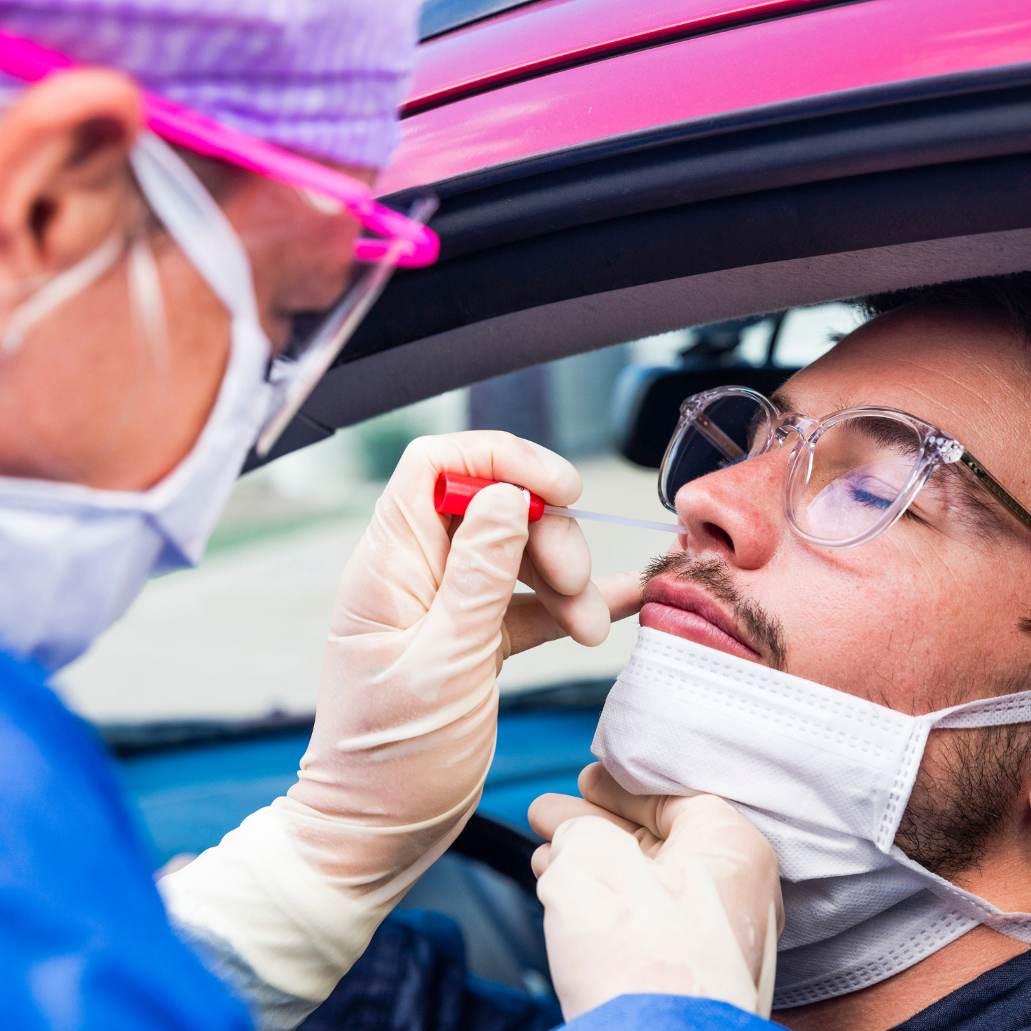 Person receiving covid test from health care professional while sitting in car